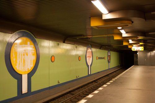 U-Bahnhof Siemensdamm 2015. Ursprünglich waren die Wände in Sichtbeton gehalten, Stationsname, Grafiken und Werbetafeln waren von roten und gelben Rahmen umgeben.